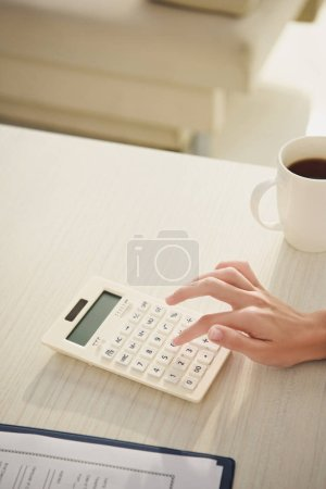 cropped view of woman counting finances on calculator at table with cup of coffee