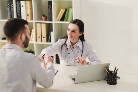 client and smiling doctor shaking hands in medical office