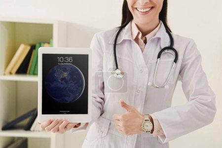 vue recadrée du docteur montrant le pouce vers le haut et la présentation ipad