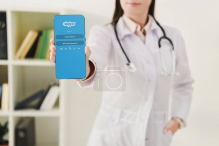 cropped view of doctor presenting smartphone with skype appliance