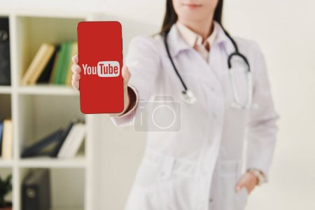 cropped view of doctor presenting smartphone with youtube logo