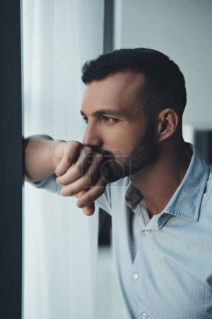 thoughtful man standing at window at home