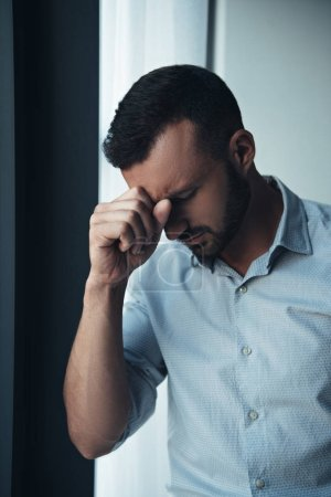 handsome lonely man in bad mood standing near window at home