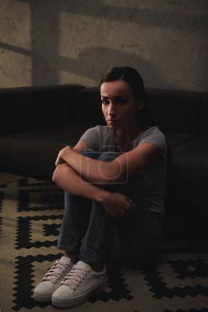 depressed woman hugging her knees while sitting on floor at home