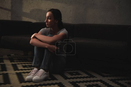 beautiful upset woman sitting on floor at home