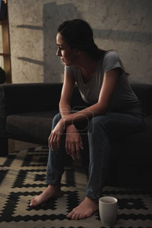 upset depressed girl sitting on sofa at home