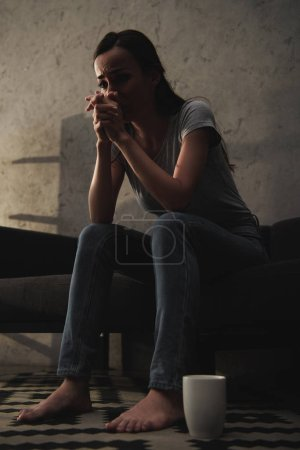Photo for Bottom view of crying woman sitting on sofa with coffee cup on floor - Royalty Free Image