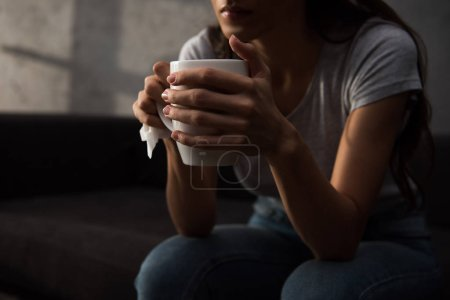 cropped view of woman holding cup of coffee
