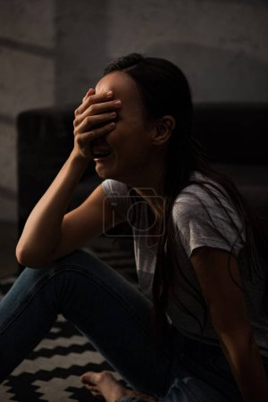 Photo for Emotional woman crying in grief at home - Royalty Free Image