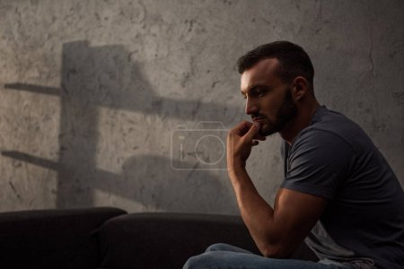 Photo for Lonely pensive man sitting on sofa at home - Royalty Free Image