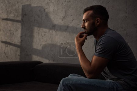 upset thoughtful man sitting on sofa