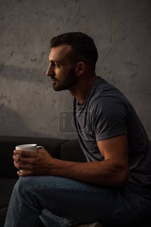 upset lonely man holding coffee cup at home