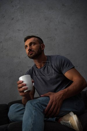 bottom view of lonely man holding coffee cup at home