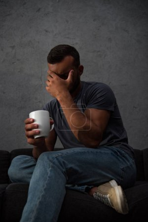 depressed crying man holding cup of coffee sitting at home