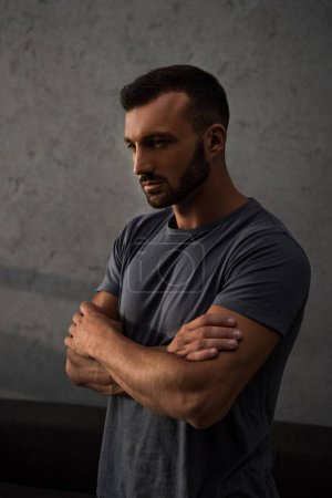 sad handsome man standing with crossed arms