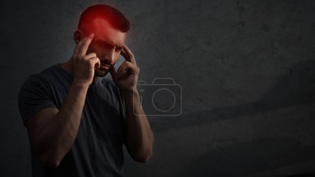 tired upset man suffering from headache with red painful point on head