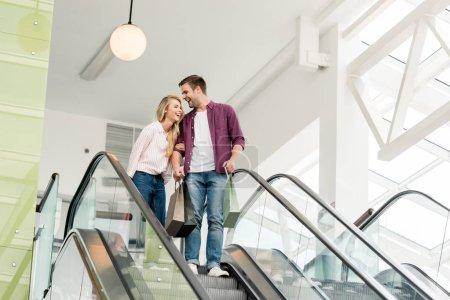 Photo pour Souriante jeune couple des acheteurs avec des sacs en papier sur l'escalator au centre commercial - image libre de droit