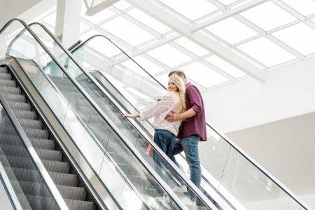 Photo pour Vue arrière du jeune couple des acheteurs avec des sacs en papier sur l'escalator au centre commercial - image libre de droit
