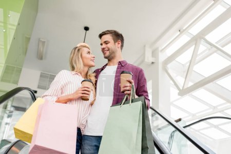 Photo for Low angle view of young couple of shoppers with paper bags and coffee cups on escalator at mall - Royalty Free Image