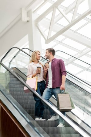 Photo for Low angle view of smiling couple of shoppers with paper bags and coffee cups on escalator at mall - Royalty Free Image