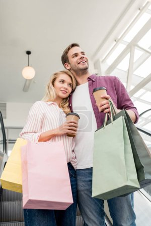 Photo pour Vue à angle bas du couple avec tasses à café jetables et sacs en papier sur escalator au centre commercial - image libre de droit
