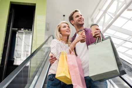 young woman with paper cup of coffee and shopping bags pointing to boyfriend on escalator at mall