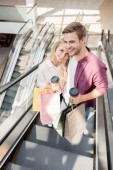 high angle view of couple with disposable coffee cups and paper bags on escalator at mall