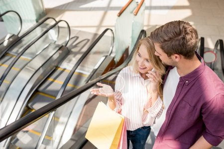high angle view of woman with shopping bags talking on smartphone while her boyfriend standing near on escalator at mall