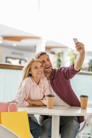 young couple at table with coffee cups taking selfie on smartphone in cafe