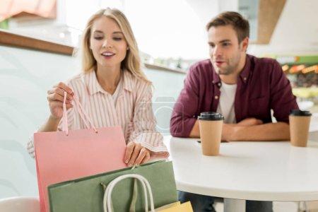 Foto de Enfoque selectivo de mujer tomando la bolsa de la silla mientras su novio sentados cerca en la mesa con tazas de café en café - Imagen libre de derechos