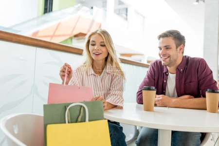 attractive woman taking shopping bag from chair while her boyfriend sitting near at table with coffee cups in cafe