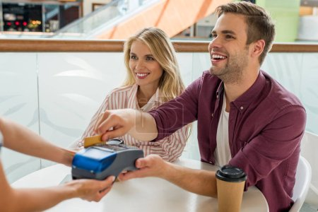 smiling young man paying by credit card on terminal while his girlfriend sitting near at table with coffee cups in cafe