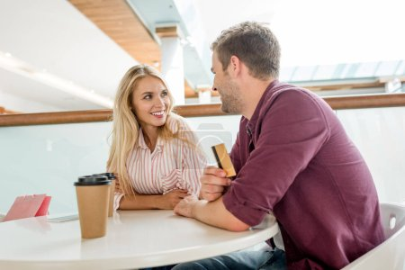 Photo for Smiling young man with credit card talking to girlfriend at table with coffee cups in cafe - Royalty Free Image