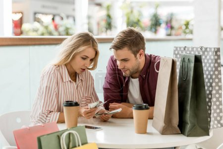 focused young couple counting cash money at table with coffee cups in cafe
