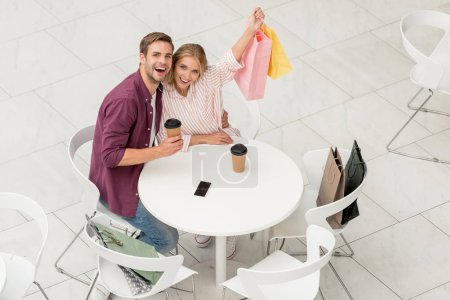 high angle view of couple showing shopping bags sitting at table with disposable cups and smartphone with blank screen in cafe