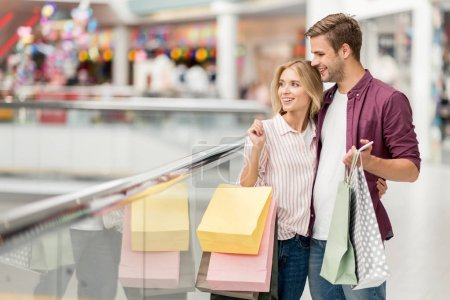 selective focus of couple with shopping bags and smartphone at shopping mall