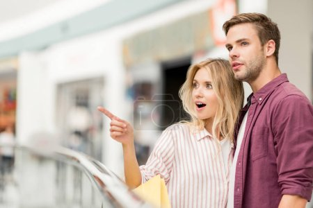 selective focus of young woman with shopping bags pointing to boyfriend at shopping mall