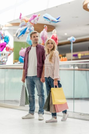 stylish couple of shoppers with paper bags standing at shopping mall