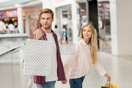 young man with shopping bags pointing by finger to girlfriend walking near at shopping mall