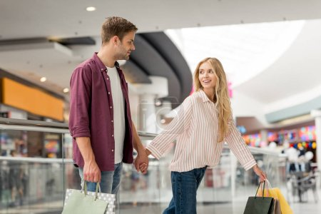 selective focus of young couple of shoppers with paper bags walking at shopping mall