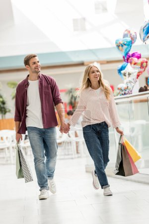 happy young couple of shoppers with paper bags walking at shopping mall