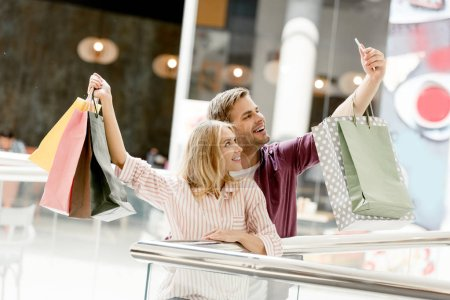 happy young couple of shoppers with taking selfie with shopping bags at mall