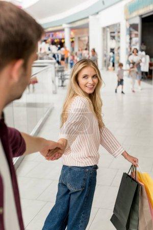 Photo pour Belle femme souriante avec des sacs de papier conduisant petit ami à la main au centre commercial - image libre de droit