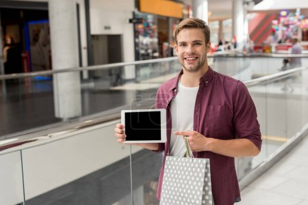young handsome man with shopping bag pointing by finger at digital tablet with blank screen at mall