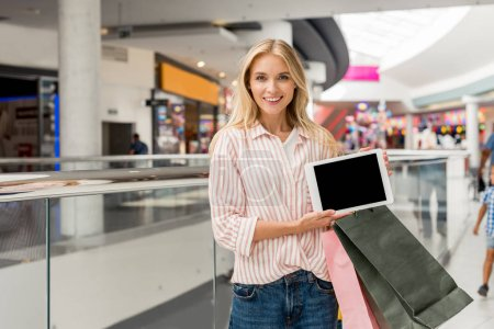 young smiling woman with shopping bags showing digital tablet with blank screen at mall