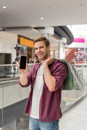 Photo pour Heureux jeune homme avec des sacs à provisions montrant des smartphone avec un écran blanc au centre commercial - image libre de droit