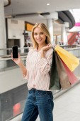 young woman with paper bags showing smartphone with blank screen at shopping mall