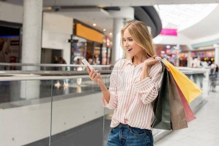 Photo pour Jeune shopper femme souriante avec des sacs en papier à l'aide de smartphone au centre commercial - image libre de droit