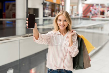 selective focus of woman with paper bags showing smartphone with blank screen at shopping mall