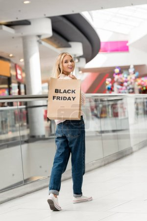 attractive young woman holding paper bag with lettering black friday and looking at camera at shopping mall